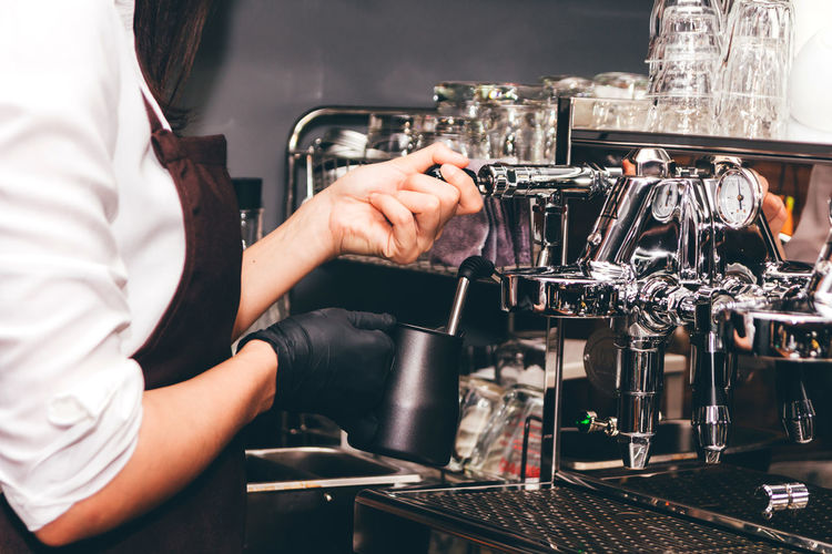 Women Barista using coffee machine for making coffee in the cafe Human Hand Occupation Coffee Maker Real People Hand Working Indoors  Coffee Shop One Person Cafe Machinery Coffee Coffee - Drink Refreshment Espresso Maker Barista Human Body Part Drink Food And Drink Serving Food And Drinks Preparation