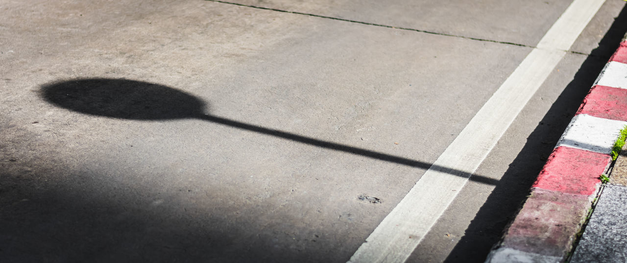 A shadow of street sign in the lain on the road. Copy Space Objects Road Shadows & Lights Sign Traffic Transport Transportation Abstract Day Floor Ground High Angle View No People Outdoors Route Safety Shadow Space Steet Street Sign Summer Sunlight Symbol Way