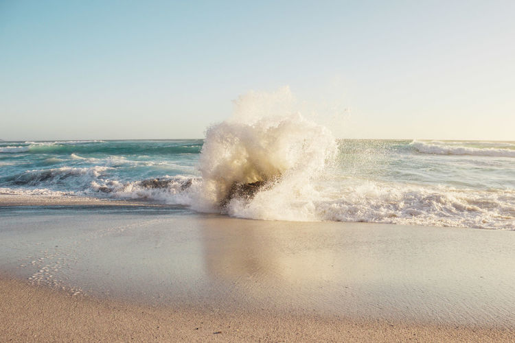Waves splashing on shore against clear sky