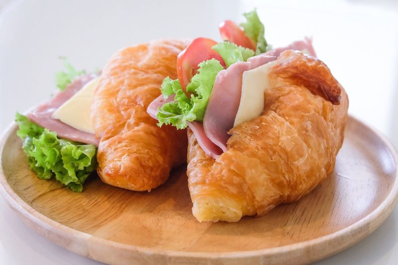 Close-up of croissants and with meat and salad on wooden plate
