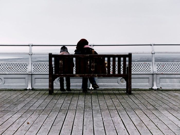 Rear view of two people overlooking calm sea