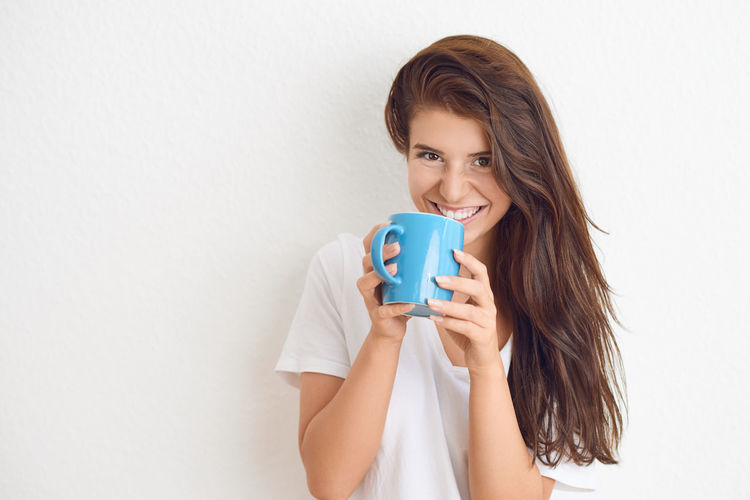 Beautiful young woman drinking coffee One Person Drink Young Adult Food And Drink Hairstyle Holding Coffee Real People Drinking Mug Brunette Happy Enjoyment Beautiful Woman Positive Emotion Smiling Happiness Portrait Looking At Camera Cheerful