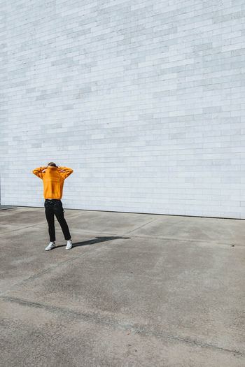 Man covering face with t-shirt while standing on road against wall