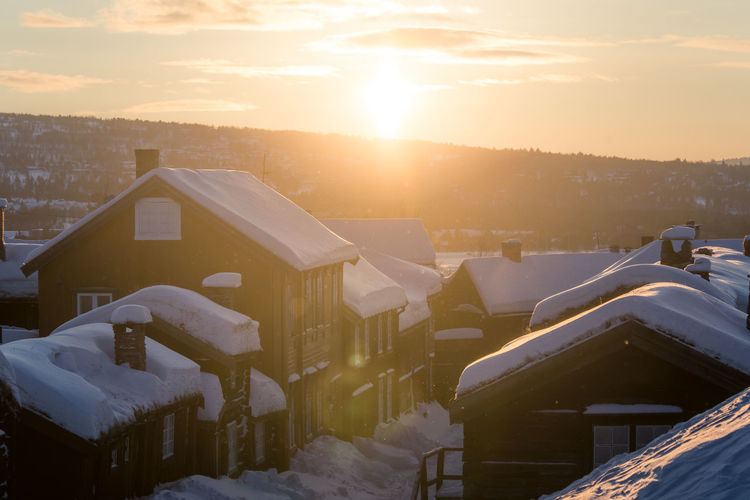 Snow Covered Houses And Buildings Against Sky During Sunset