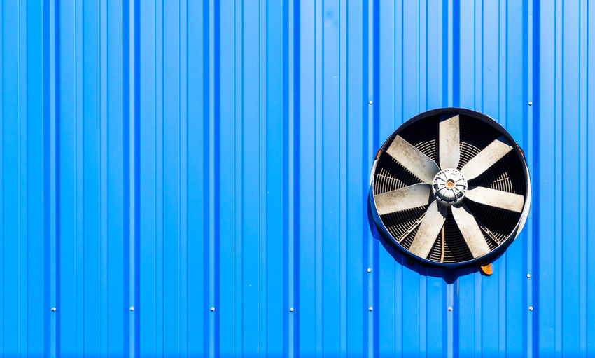Exhaust fan on blue corrugated iron