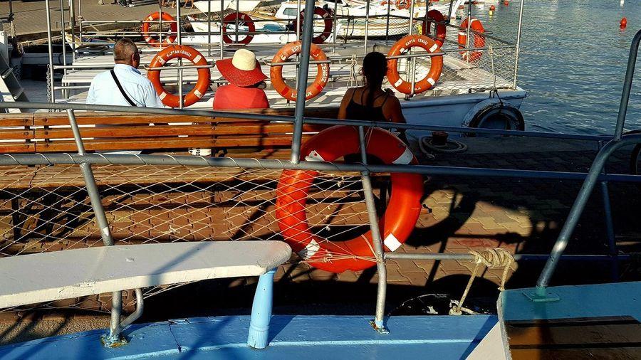Man sitting on boat against sea