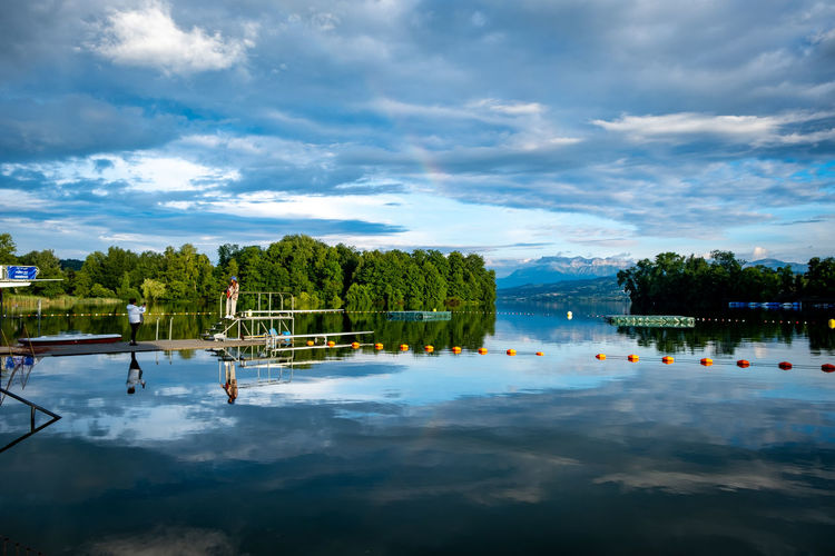 Swimming pool by lake against sky