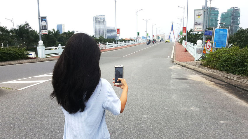 Woman taking selfie with smartphone in the middle of the street in Da Nang, Vietnam. Bridges City Communication Da Nang Holding Mobile Phone One Woman Only Outdoors Rear View Road Selfies Smart Phone Street Technology Traffic Vietnam Walking Wireless Technology