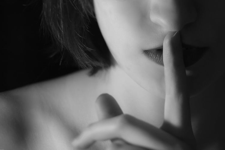 Close-up of woman with finger on lips against black background