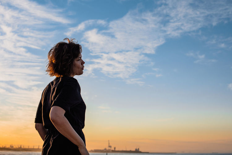 Midsection of woman standing against sky during sunset