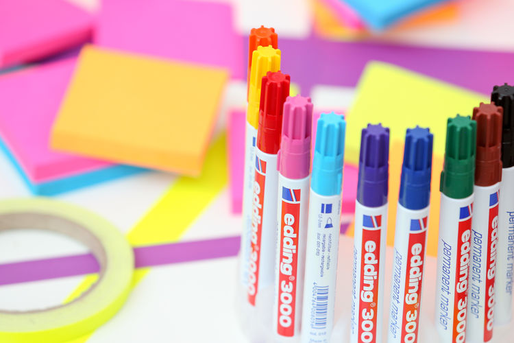 Close-up of colorful felt-tip pens by adhesive papers on table
