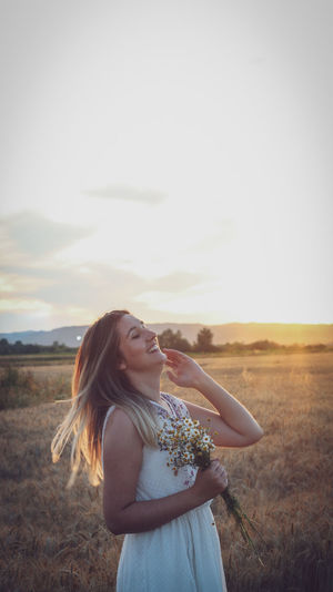 Beautiful woman standing on field against sky