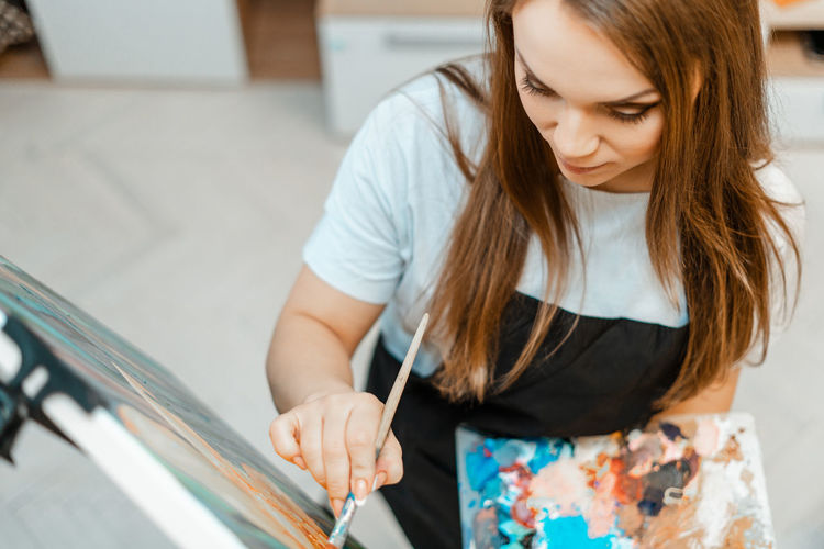 High angle view of beautiful woman painting on canvas