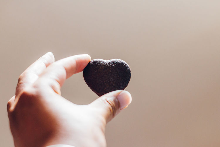 Close-up of man holding heart shape brown cookie against white background