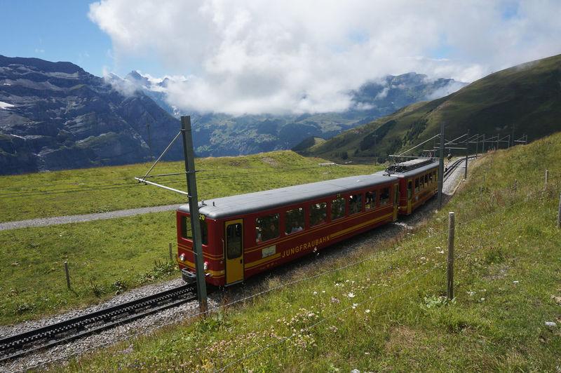 Train by railroad tracks on field against sky