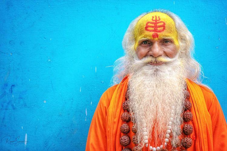 Portrait of sadhu against wall