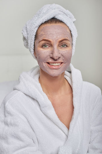 Woman at a spa with a face mask Bathrobe Bathroom Beautiful Woman Beauty Mask Beauty Spa Beauty Treatment Best Ager Clay Face Face Mask Health Spa Human Face Indoors  Lifestyles Looking At Camera Middle-aged Portrait Smiling Towel Wrapped In A Towel