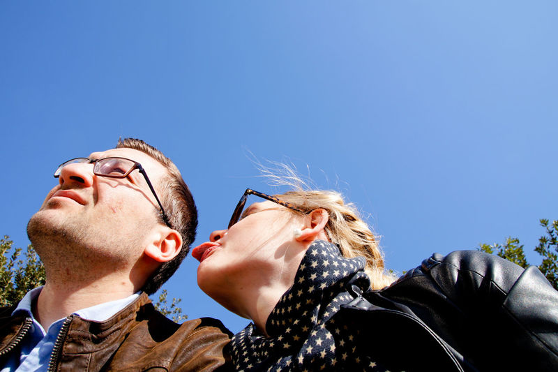 Low angle view of woman sticking out tongue while sitting by boyfriend against clear blue sky