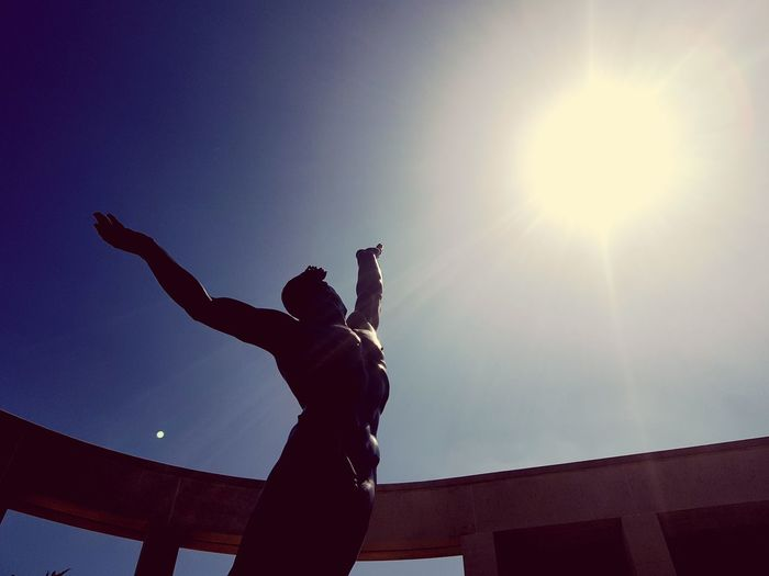 Low angle view of silhouette person against sky on sunny day