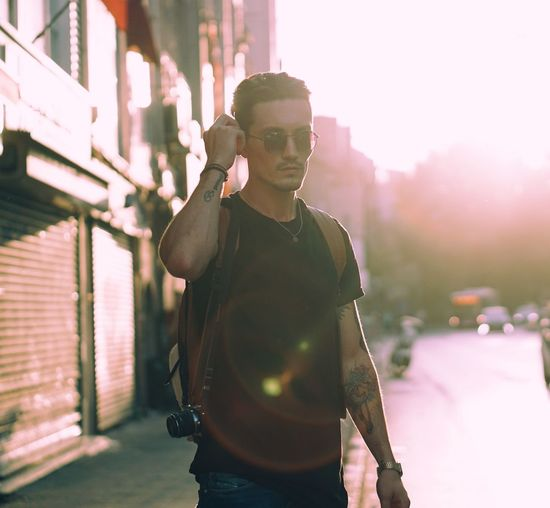 Standing Young Adult Lifestyles Leisure Activity Front View Person Casual Clothing Focus On Foreground Sunbeam Outdoors Bright Handsome Plant Day Green Color Dovme Tattoos Sky Tattoo Sunset Nature Close-up Tranquility Branch Orange Color