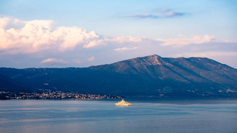 A ferry in the bay after Sunset in Korcula, Croatia. Croatia Ferry Korčula Bay Beauty In Nature Cloud - Sky Day Korcula Island Mode Of Transportation Mountain Mountain Range Nature Nautical Vessel No People Non-urban Scene Outdoors Scenics - Nature Sea Sky Sunset Tranquil Scene Tranquility Transportation Water Waterfront