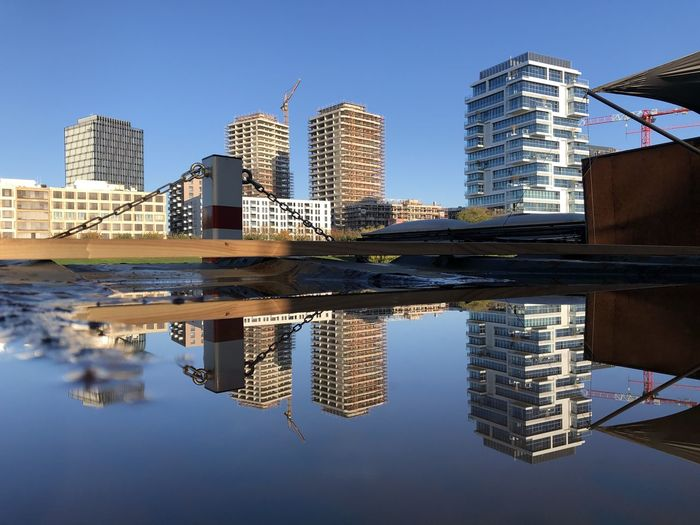 Reflection of buildings in city against clear sky