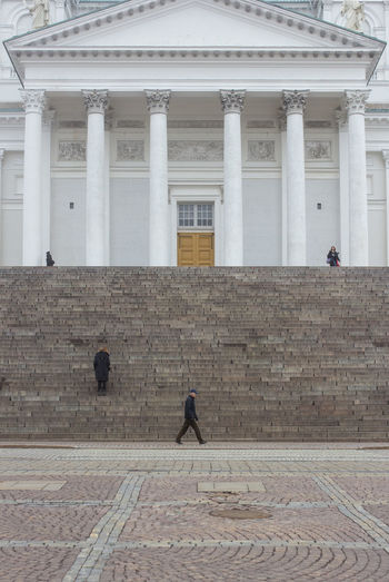 People walking in front of historical building
