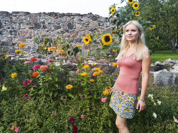 Blond woman standing by sunflowers in Estonia. Beautiful Woman Blond Hair Day Flower Nature One Person Outdoors People Plant Real People Standing Standing Summer Sunflower Wall Young Adult Young Women