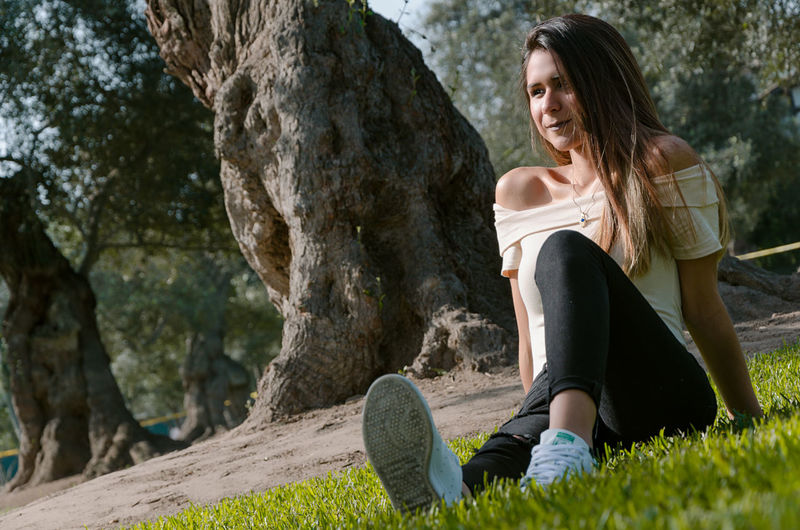 Tilt image of smiling young woman sitting against trees in park