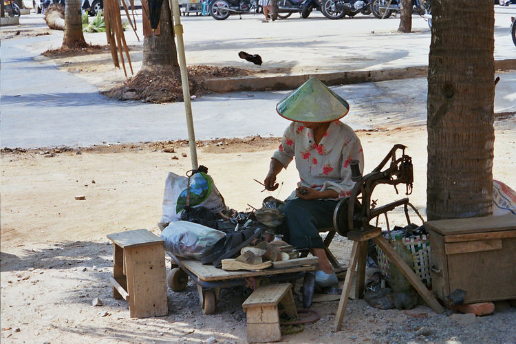 Shoemaker Working While Sitting Over Seat On Footpath