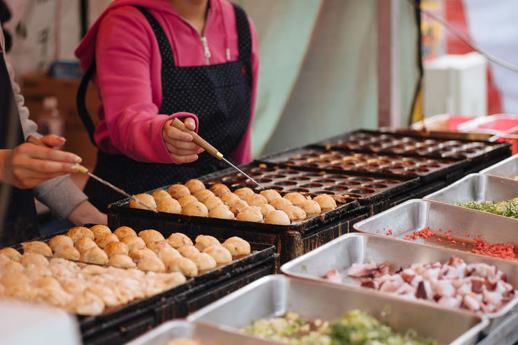 Midsection of woman preparing japanese street food at market