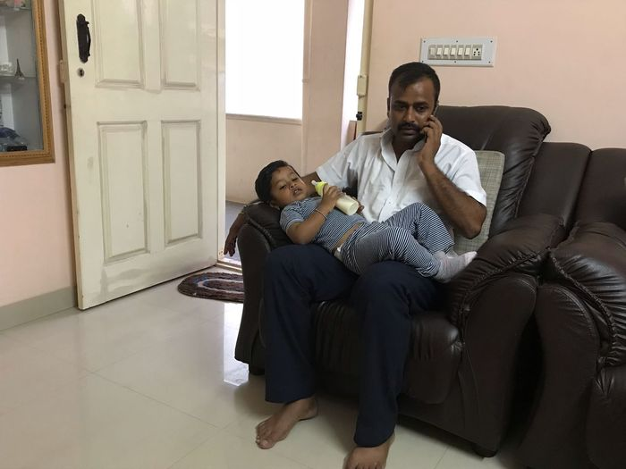 Father answering mobile phone while son lying on his laps at home