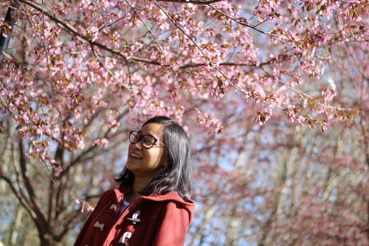 Young woman by flowering tree