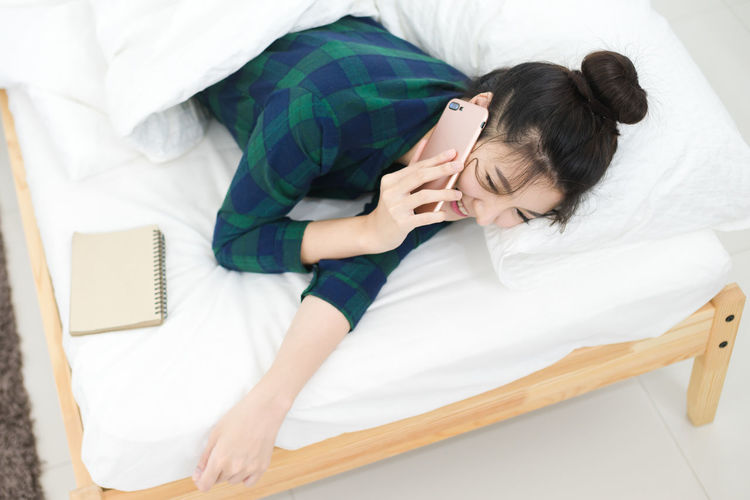 High angle view of woman answering smart phone while lying on bed at home