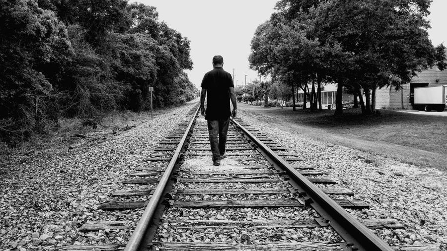 Rear View Of A Man Walking On Railway Track