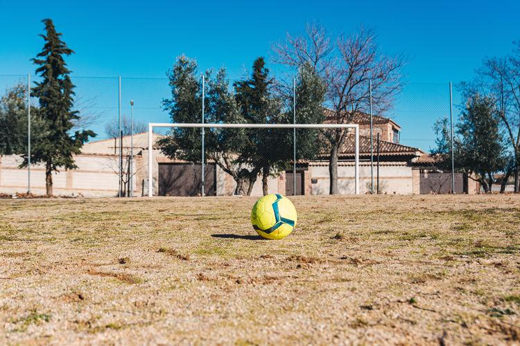 Soccer ball on field against blue sky