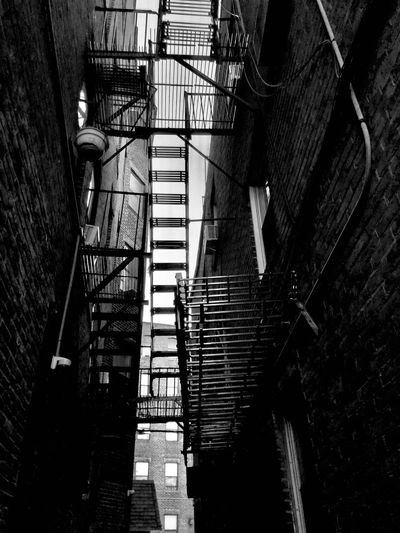 Low angle view of fire escape amidst old buildings in city