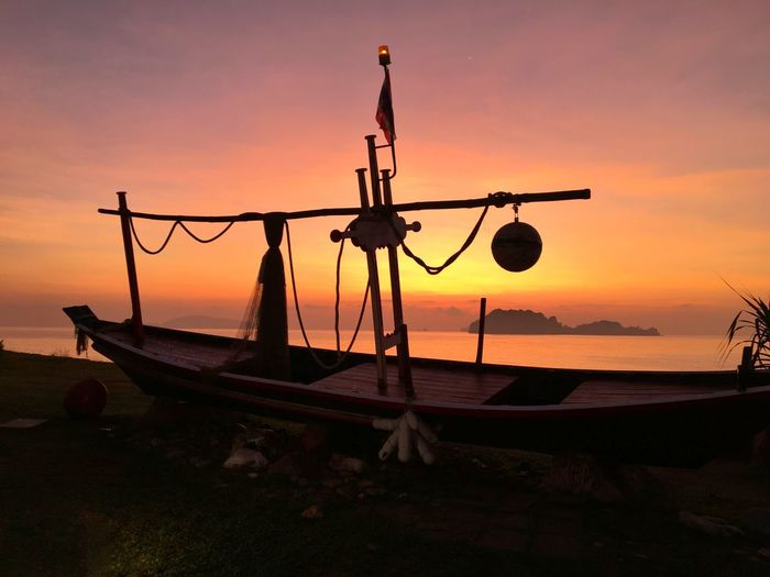 Silhouette ship moored on beach against sky during sunset