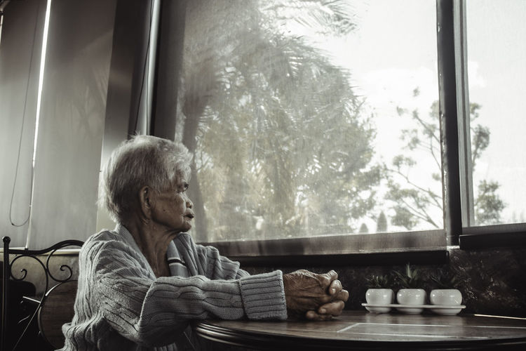 Old woman looking through window at home. concept loneliness, dementia, abuse, sadness.