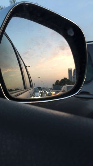Reflection of sky on side-view mirror of car