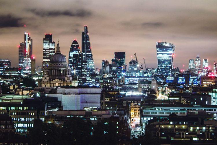Illuminated modern cityscape against sky at night
