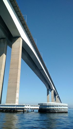 Low Angle View Of Bridge Over River Against Blue Sky
