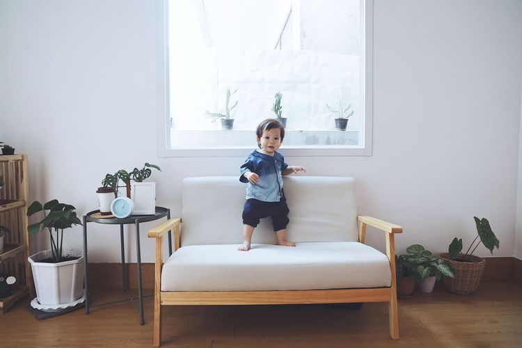 Full length of boy on table at home