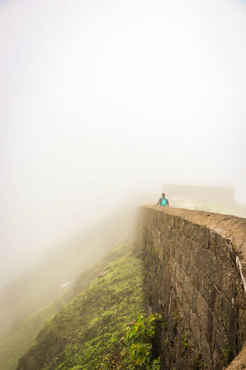 Rear View Of Man Hiking On Fort During Foggy Weather
