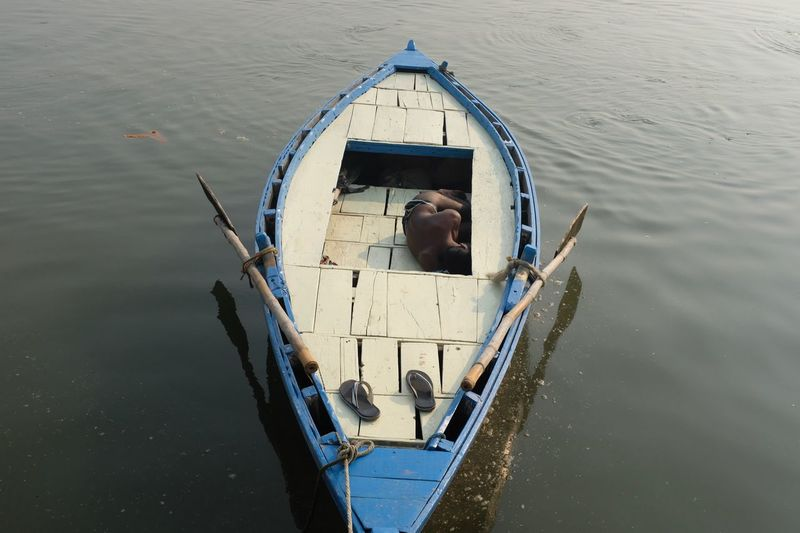 High angle view of shirtless man sleeping on boat in lake