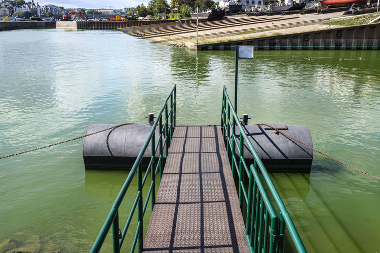 A metal platform protruding from the river bank on air tanks, a pier to the entrance to the ship.