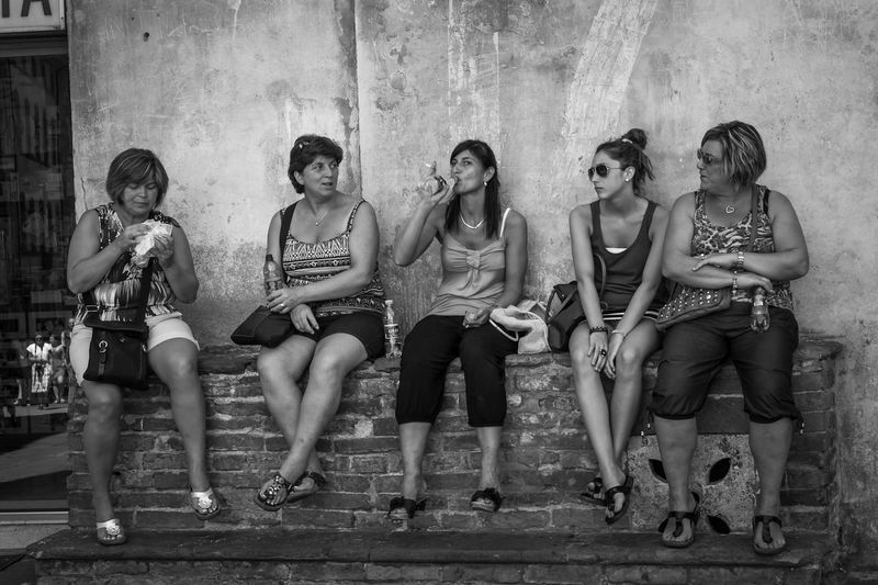 Group of ladies taking a rest in the shade, a hot summer's day in Siena, Italy. Adult Adults Only Attitude Day Drink Drinking Friendship Front View Full Length Group Of People Legs Apart Looking At Camera Outdoors People Portrait Quenching My Thirst  Relaxation Sitting Young Adult Young Women