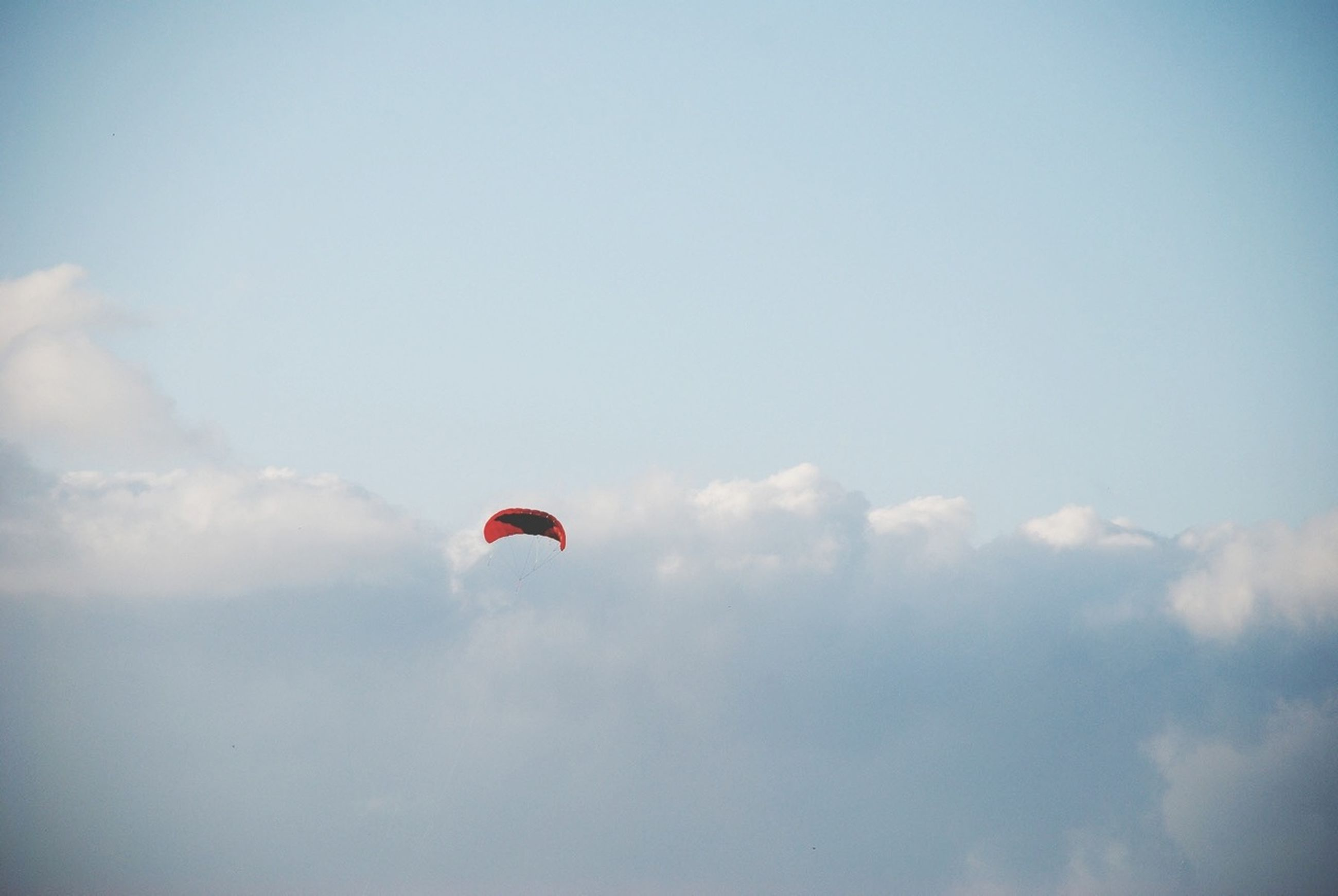 low angle view, mid-air, sky, flying, parachute, cloud - sky, adventure, extreme sports, paragliding, freedom, leisure activity, sport, cloud, exhilaration, hot air balloon, unrecognizable person, outdoors, day