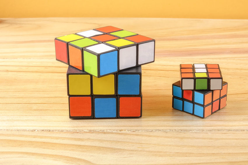 RUBIK'S CUBE , CREATIVITY TOY Creativity Rubik Cube Block Block Shape Childhood Choice Close-up Cube Shape Design Geometric Shape Indoors  Intelligence Large Group Of Objects Multi Colored Puzzle  Rubik Shape Stack Still Life Table Toy Toy Block Variation Wood - Material