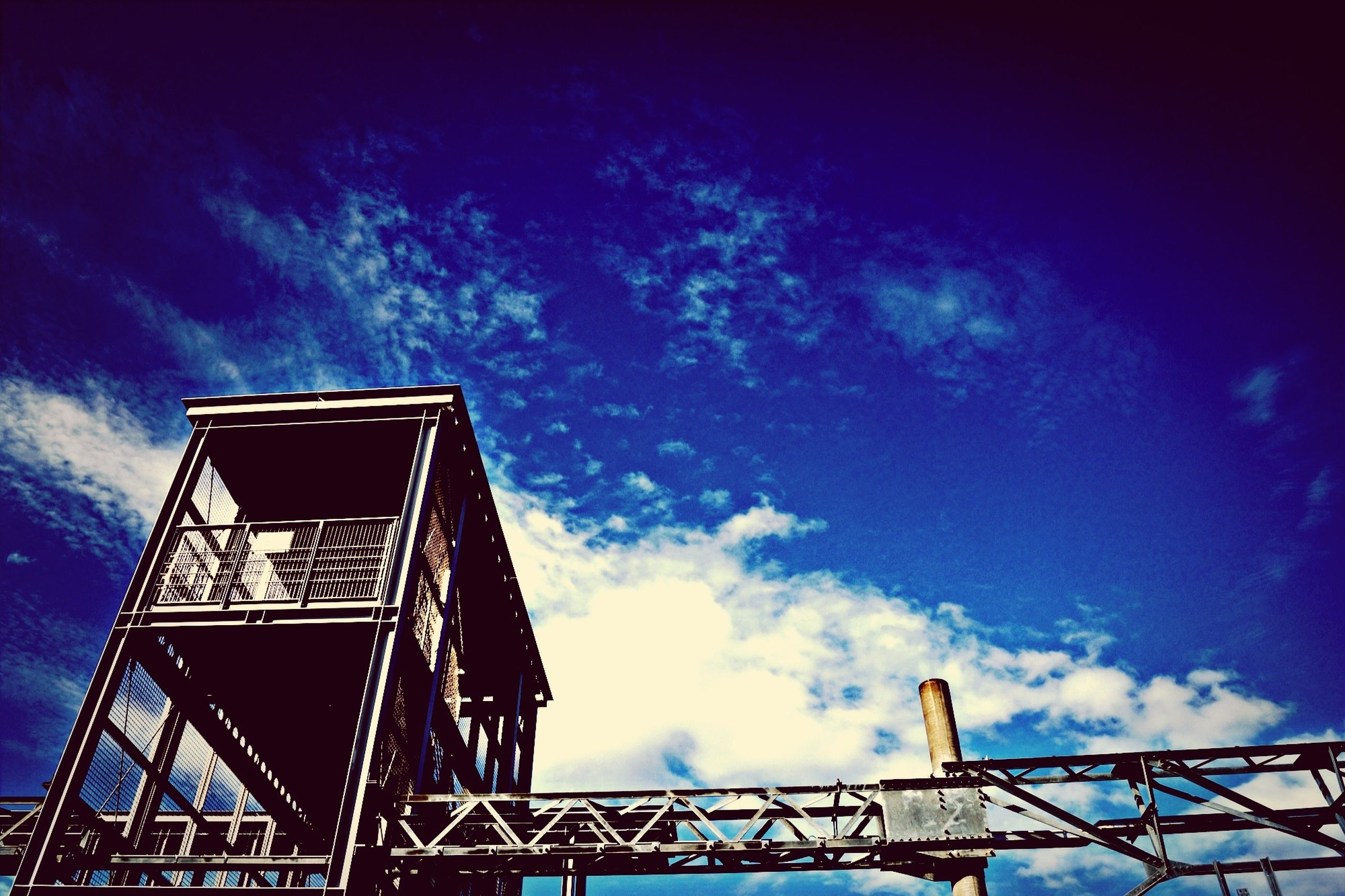 low angle view, sky, built structure, architecture, cloud - sky, metal, blue, cloud, cloudy, metallic, high section, building exterior, no people, outdoors, railing, day, connection, silhouette, tower, engineering